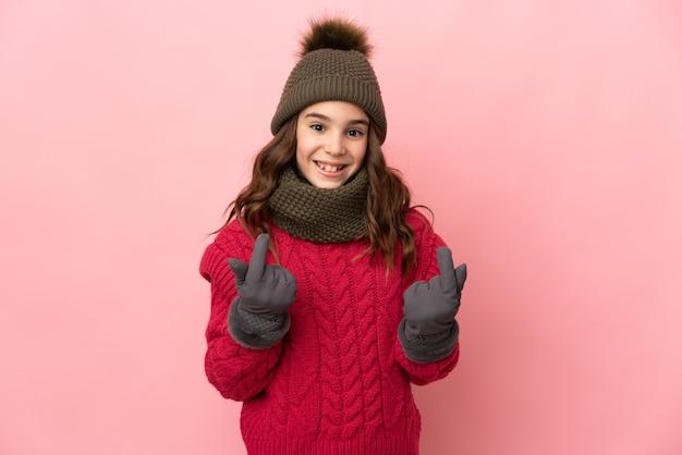 お金のジェスチャーを作るピンクの背景に分離された冬の帽子を持つ少女