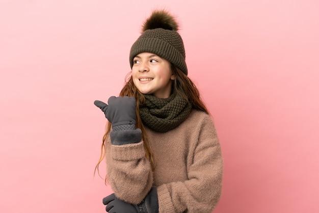 제품을 제시하기 위해 측면을 가리키는 분홍색 배경에 격리된 겨울 모자를 쓴 어린 소녀