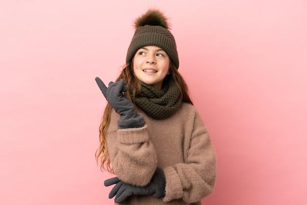 좋은 아이디어를 가리키는 분홍색 배경에 고립 된 겨울 모자와 어린 소녀