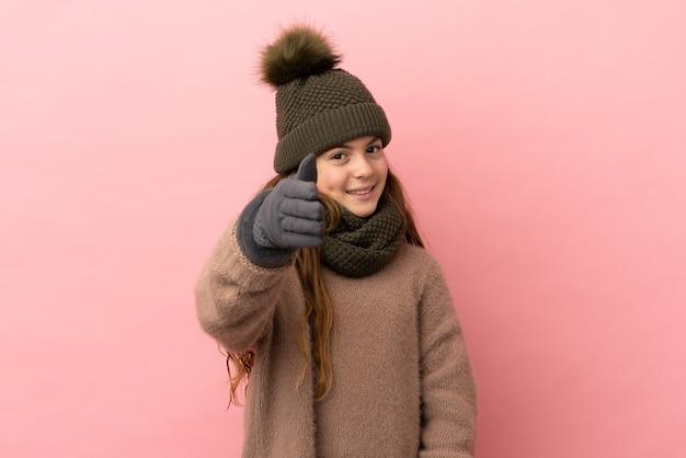 분홍색 배경에 격리된 겨울 모자를 쓴 어린 소녀가 좋은 거래를 성사시키기 위해 악수를 하고 있다