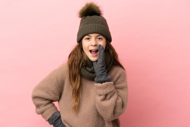 Маленькая девочка в зимней шапке, изолированные на розовом фоне, кричит с широко открытым ртом