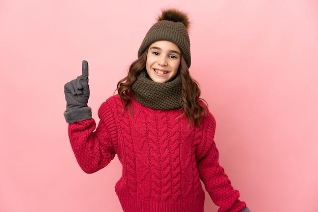 분홍색 배경에 고립 된 겨울 모자와 어린 소녀는 최고의 기호에 손가락을 보여주는