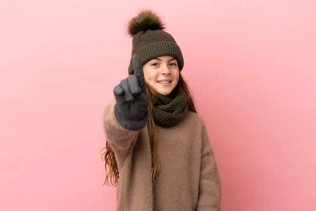 Маленькая девочка в зимней шапке на розовом фоне показывает и поднимает палец