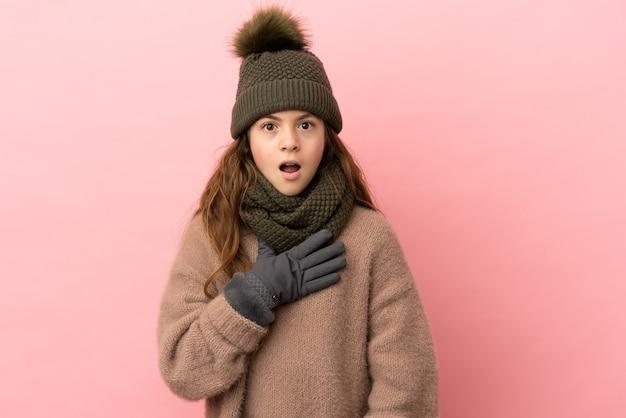 분홍색 배경에 격리된 겨울 모자를 쓴 어린 소녀는 오른쪽을 보고 놀라고 충격을 받았습니다
