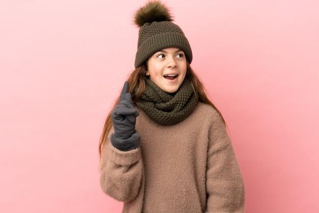분홍색 배경에 격리된 겨울 모자를 쓴 어린 소녀가 손가락을 가리키는 아이디어를 생각하고 있습니다
