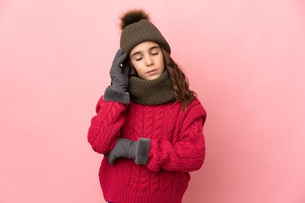 頭痛とピンクの背景に分離された冬の帽子を持つ少女 Premium写真
