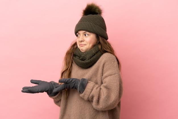 분홍색 배경에 겨울 모자를 쓴 어린 소녀가 옆을 바라보면서 놀란 표정을 하고 있다