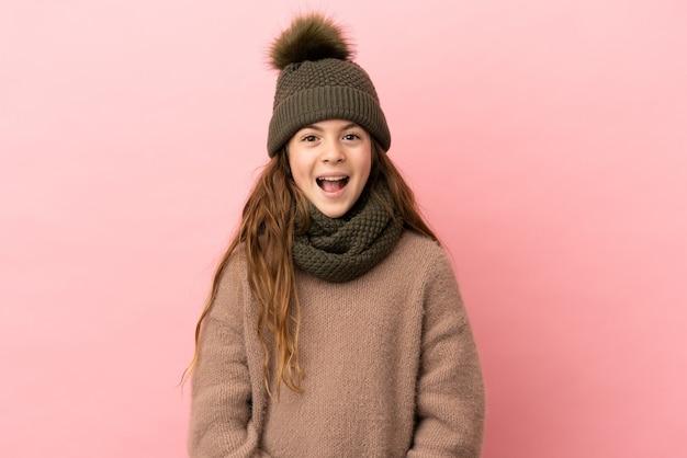驚きの表情でピンクの背景に分離された冬の帽子を持つ少女