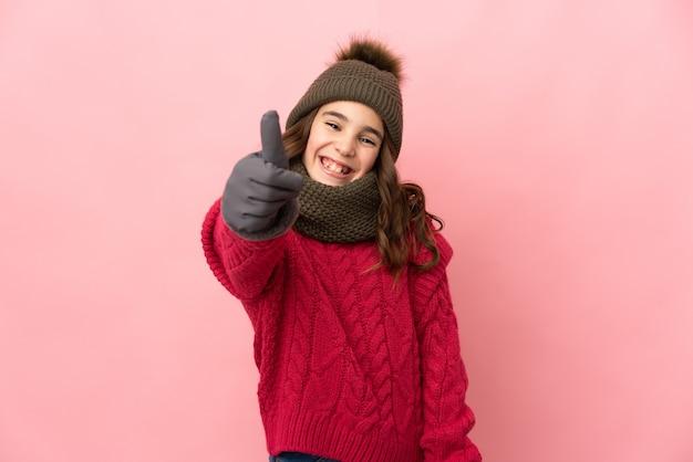좋은 일이 일어났기 때문에 엄지 손가락으로 분홍색 배경에 고립 된 겨울 모자와 어린 소녀