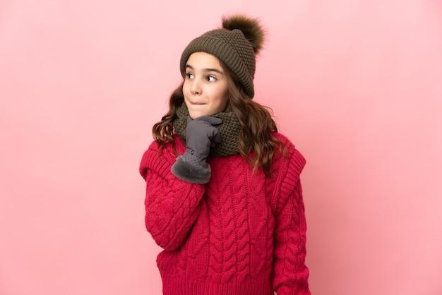 의심과 생각을 갖는 분홍색 벽에 고립 된 겨울 모자와 어린 소녀