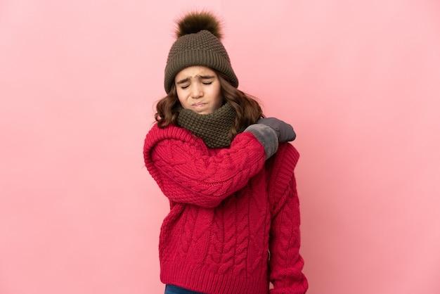 Маленькая девочка в зимней шапке изолирована на розовой стене и страдает от боли в плече из-за того, что приложила усилие