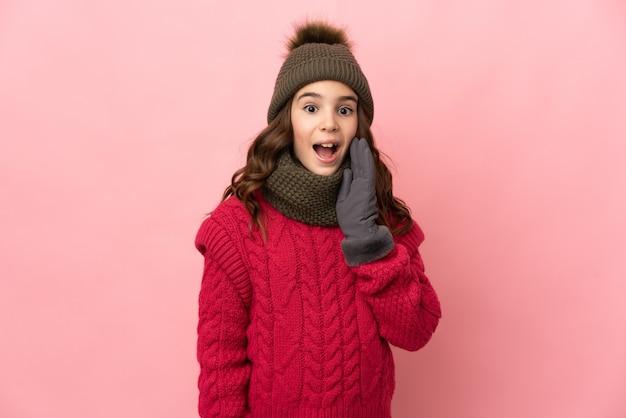Маленькая девочка в зимней шапке изолирована на розовой стене с удивленным и шокированным выражением лица