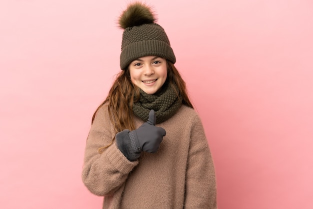 Little girl with winter hat isolated on pink background giving a thumbs up gesture