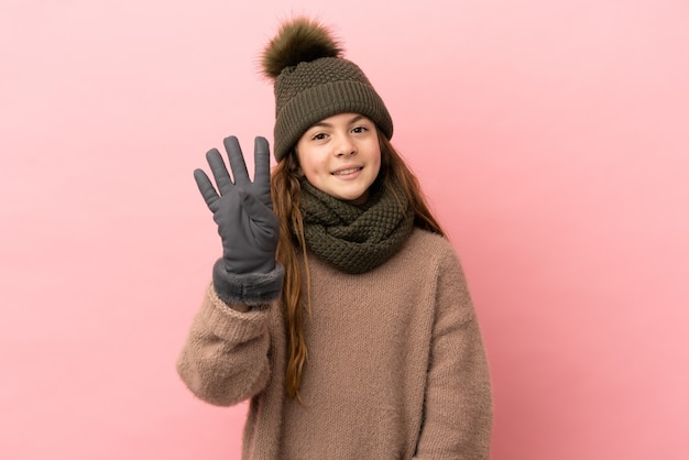 Little girl with winter hat isolated on pink background happy and counting four with fingers