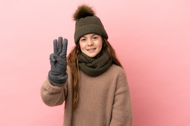 Little girl with winter hat isolated on pink background happy and counting three with fingers