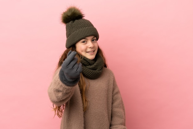 Little girl with winter hat isolated on pink background making money gesture