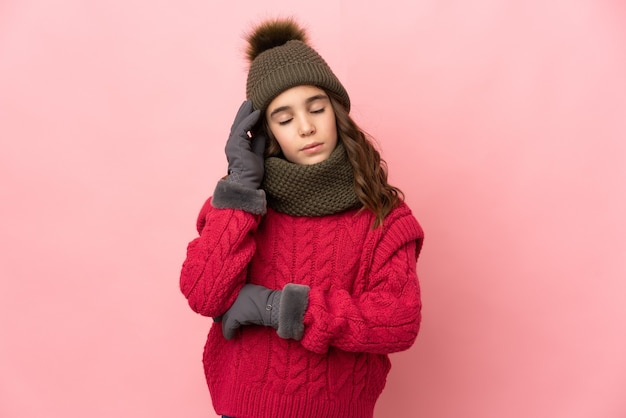 Little girl with winter hat isolated on pink background with headache