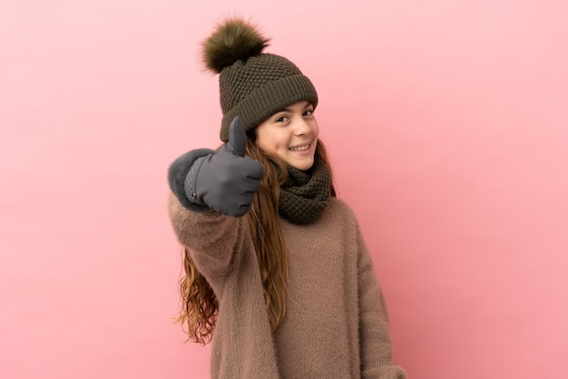 Little girl with winter hat isolated on pink background with thumbs up because something good has happened