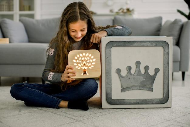Маленькая девочка с деревянной ночной лампой, сидя в современной уютной светлой гостиной дома.