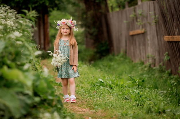 Little girl with a wreath of flowers on her head for a walk