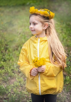 Little girl with a wreath of yellow dandelions on her head