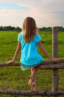 A little girl without shoes sits on a wooden fence in a meadow in summer