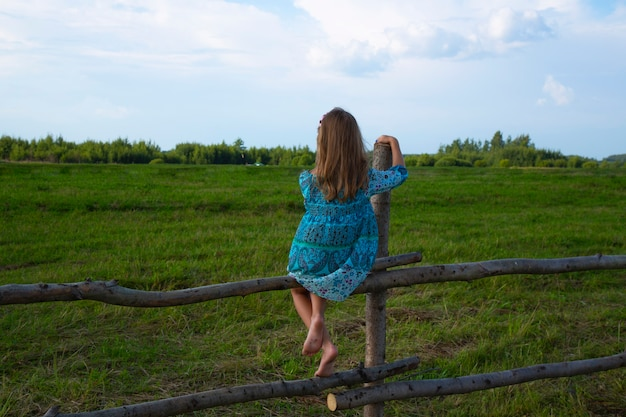 Little girl without shoes sits on a wooden fence in a meadow