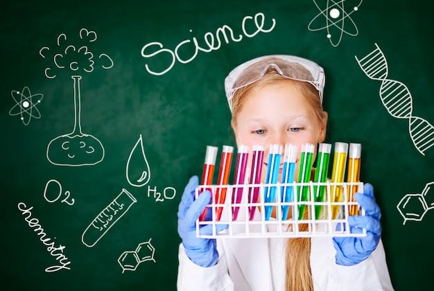 Маленькая девочка, работающая в химической лаборатории