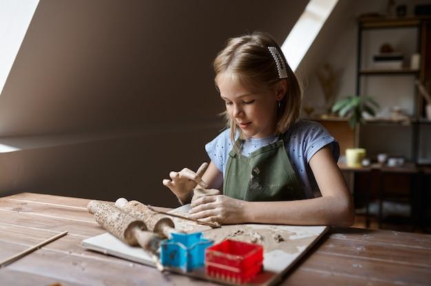 Маленькая девочка работает с глиной за столом, ребенок в мастерской. урок в художественной школе. юный мастер народных промыслов, приятное увлечение, счастливое детство.