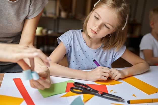 Маленькая девочка работает с цветной бумагой в мастерской