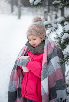 Little girl wrapped in a blanket drinking tea in the winter forest