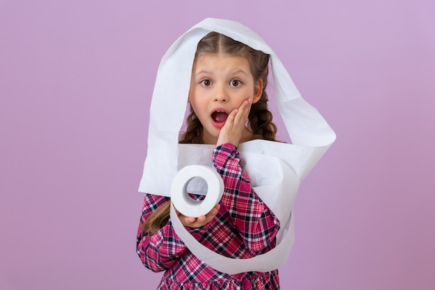 A little girl wrapped in toilet paper is surprised with her mouth wide open.