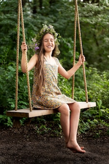 Little girl in a wreath of flowers rides on a swing and laughs