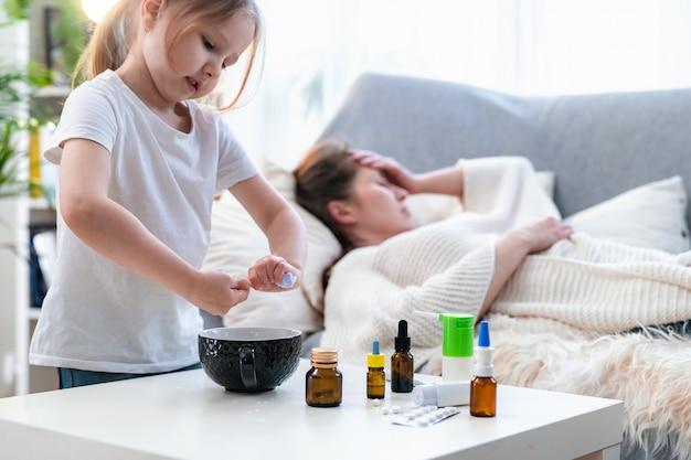 小さな女の子が水からナプキンを絞り、病気の母親の頭につけます。