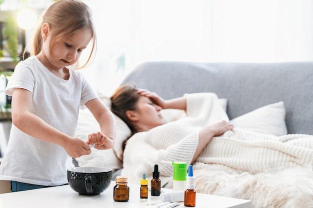 小さな女の子が水からナプキンを絞り、病気の母親の頭にそれを置く
