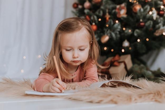 小さな女の子がサンタクロースに手紙を書くクリスマスの奇跡のクリスマスツリーギフト冬のコンセプト