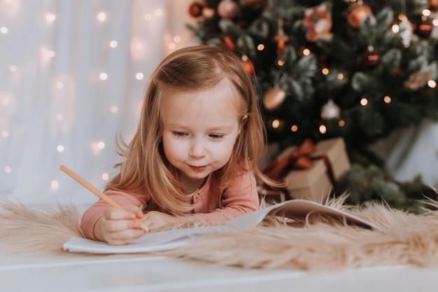 小さな女の子がサンタクロースに手紙を書くクリスマスの奇跡のクリスマスツリーの贈り物