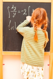 Little girl writes on the blackboard