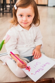 Little girl writing happy mothers day on paper