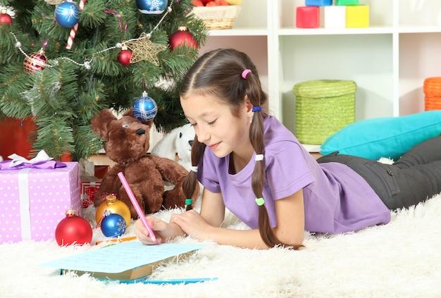 크리스마스 트리 근처 산타에게 편지를 쓰는 어린 소녀