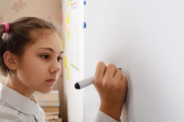 가정 과제를 수행하는 동안 보드에 무언가를 쓰는 어린 소녀
