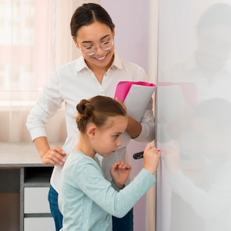 Little girl writing on a white board next to teacher