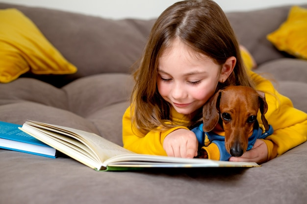 Little girl in yellow clothes is reading a book lying on the bed with a dwarf dachshund education