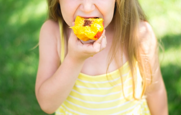 Little girl in yellow dress eating peach, close-up