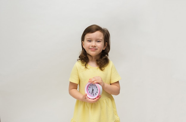 A little girl in a yellow dress holds a table clock alarm clock on a white background with a place for text