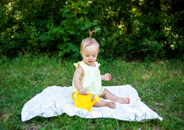A little girl in a yellow dress sits on a white blanket with a watering can in nature