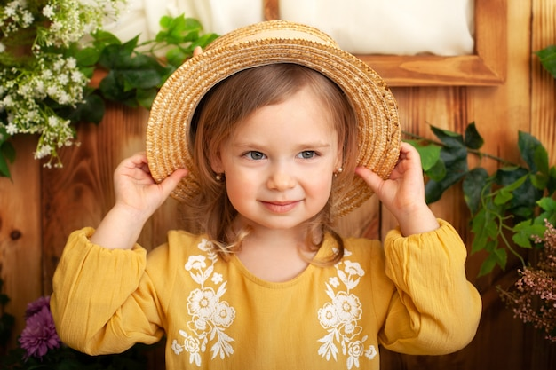 Little girl in a yellow dress smiles and holds a straw hat. childhood concept. portrait of cute little blond girl in countryside, summertime. beautiful child in spring garden. rustic.  gardening