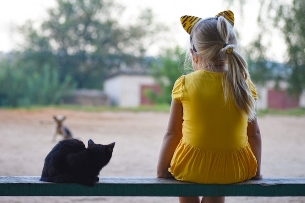 A little girl in a yellow dress with a little black cat is sitting on a bench and looking at a dog, rear view