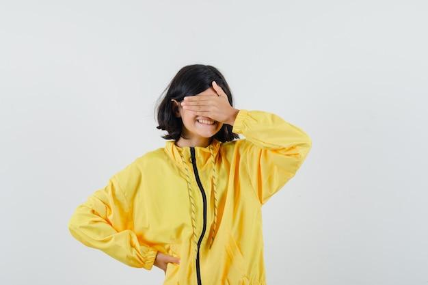 Bambina in felpa con cappuccio gialla tenendo la mano sugli occhi e guardando gioioso, vista frontale.