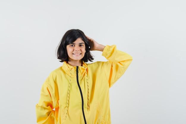 Bambina in felpa con cappuccio gialla che tiene la mano sulla testa e che sembra allegra, vista frontale.